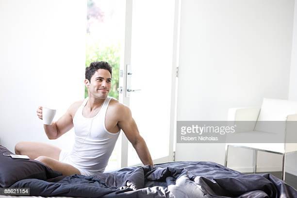 Man drinking coffee in bedroom in morning