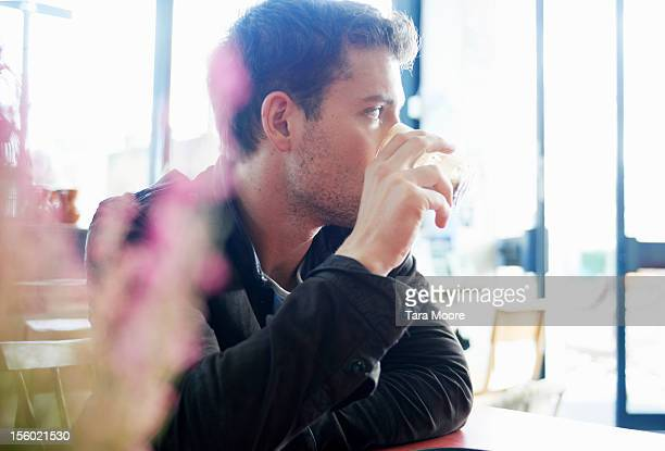 man drinking coffee in cafe