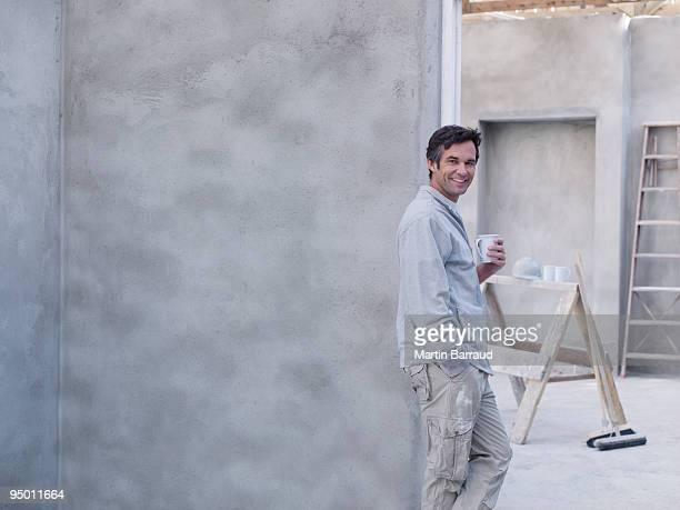 Man drinking coffee in house under construction