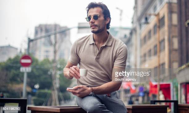 man drinking coffee in sidewalk cafe - polo shirt stock pictures, royalty-free photos & images