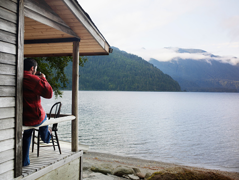 Man drinking coffee on front porch of lake cabin - gettyimageskorea