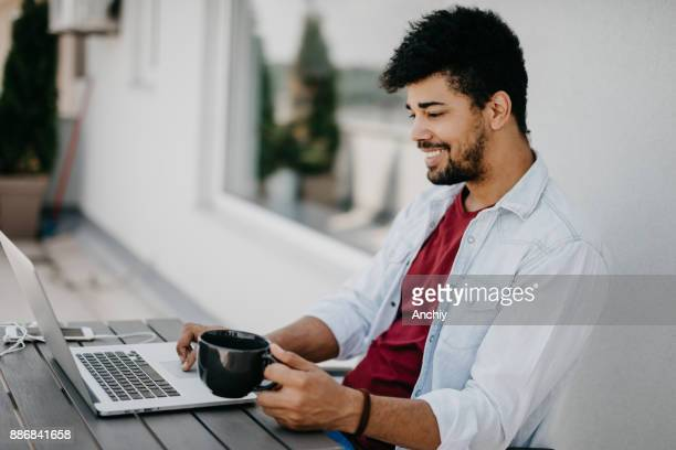 Man drinking coffee on the balcony while working on the computer.