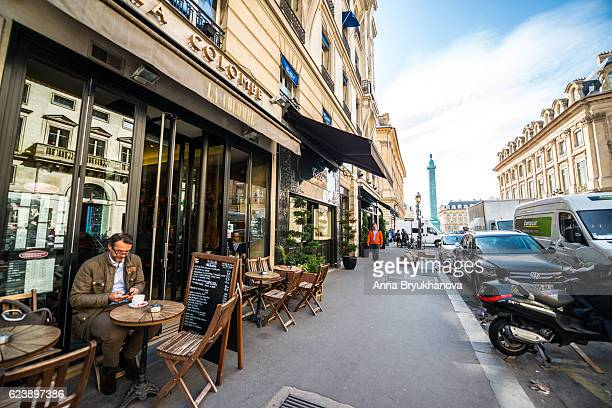 Man drinking coffee outdoors in Paris cafe, France
