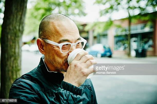 Man drinking coffee while running errands