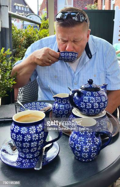 Man Drinking Coffee While Sitting By Crockery On Table In Yard