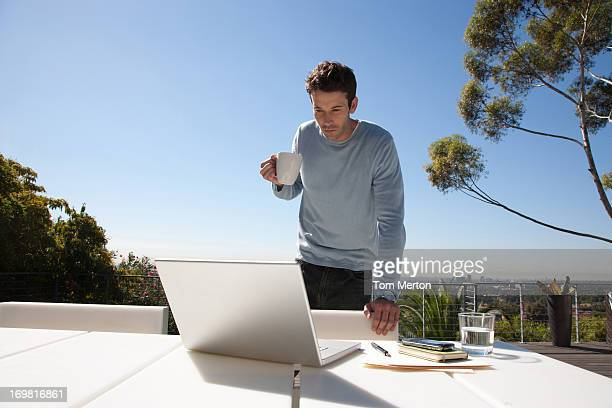Man drinking coffee with working from home on balcony