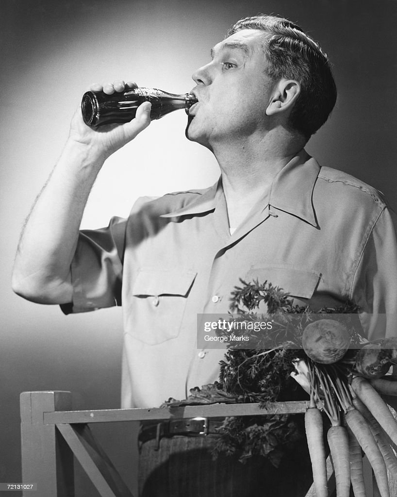 Man drinking cola from bottle in studio (B&W) : Stock Photo