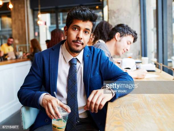 Man drinking cold beverage in cafe