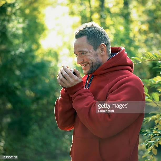 Homme de boire de tasse de café en forêt
