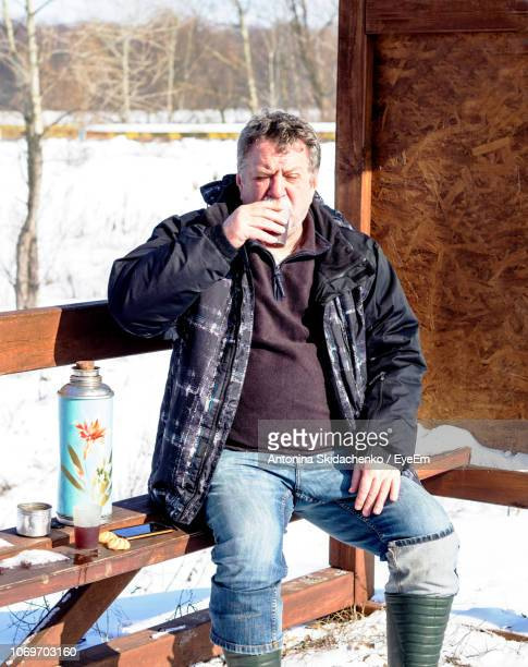 Man Drinking Drink While Sitting On Bench During Winter