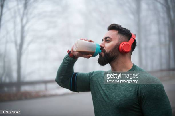 man drinking energy drink after exercising. - protein drink stock pictures, royalty-free photos & images