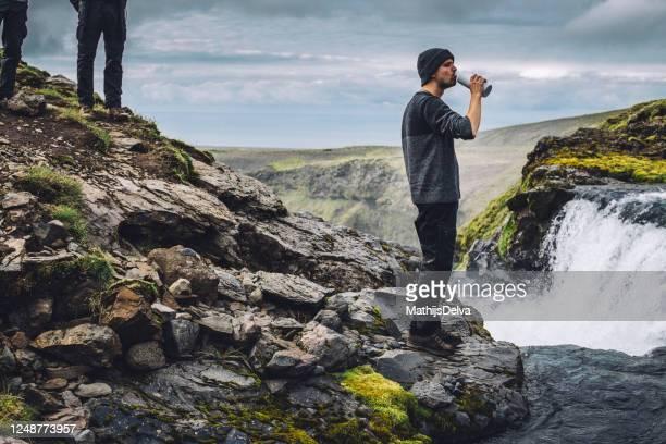 man drinking fresh water from a river near landmannalaugar, fjallabak nature reserve, south central iceland, iceland - nature reserve stock-fotos und bilder