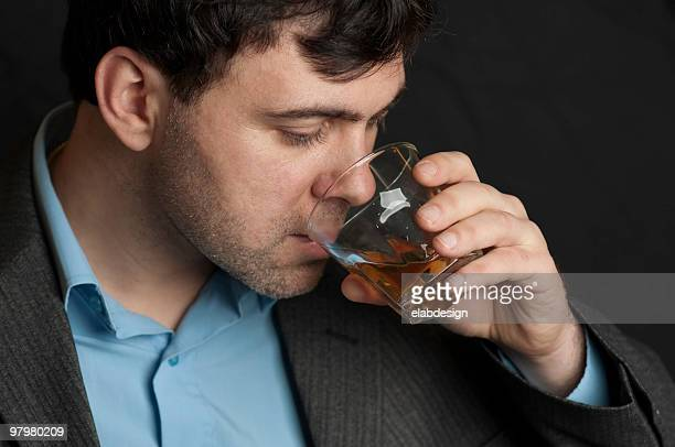 Man drinking from a glass of whiskey