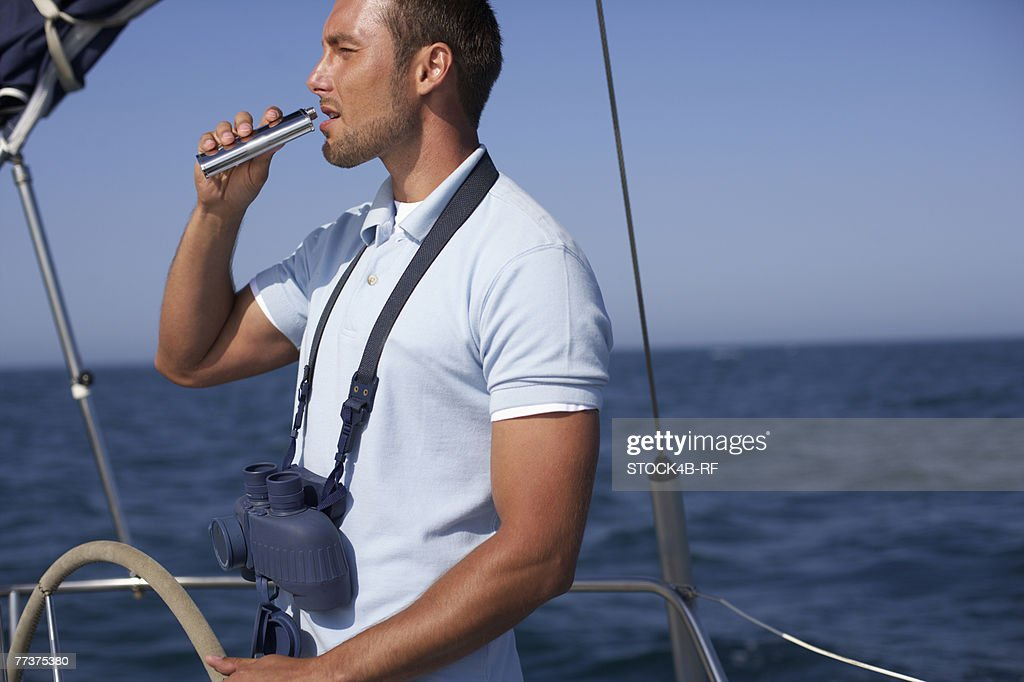 Man drinking from a pocket flask, side view, truncated : Photo