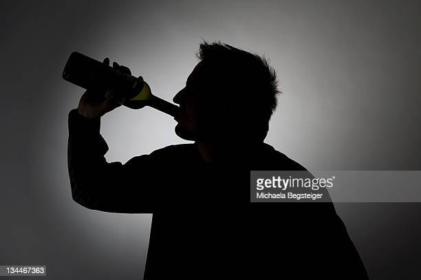 Man drinking from a wine bottle, silhouette