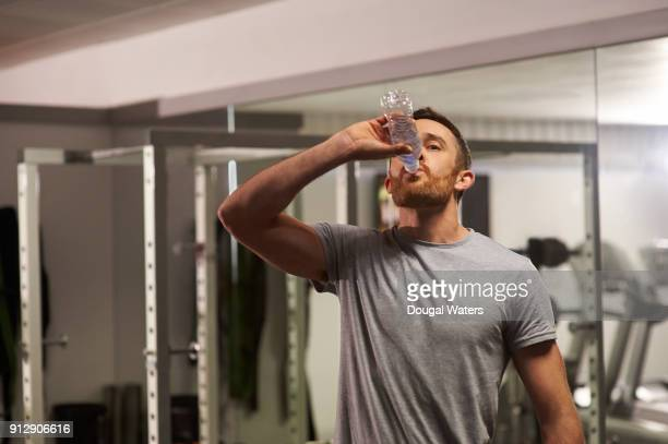 Man drinking from bottle of water at gym.