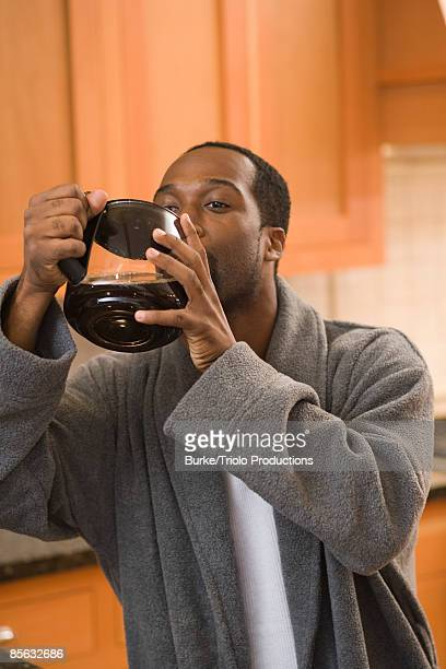 Man drinking from coffee pot