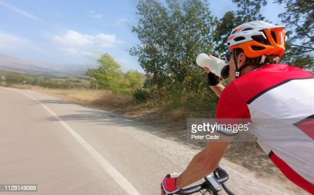 man drinking from water bottle while cycling - road race stock pictures, royalty-free photos & images