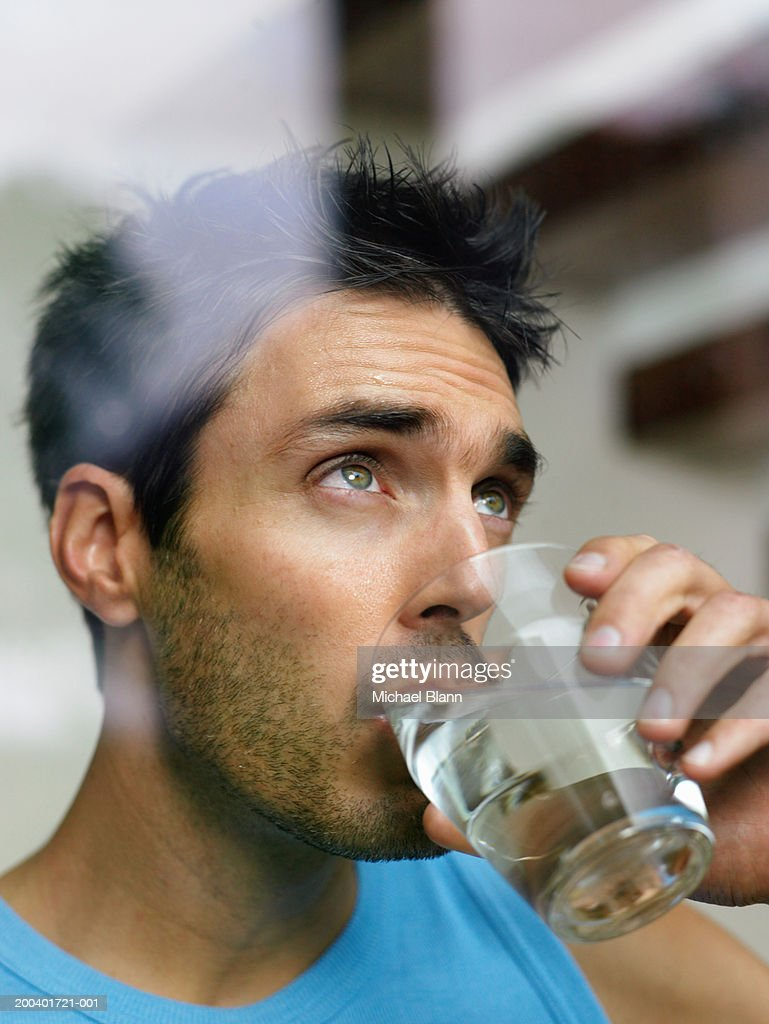 Man drinking glass of water, view through window, close-up : Stock Photo