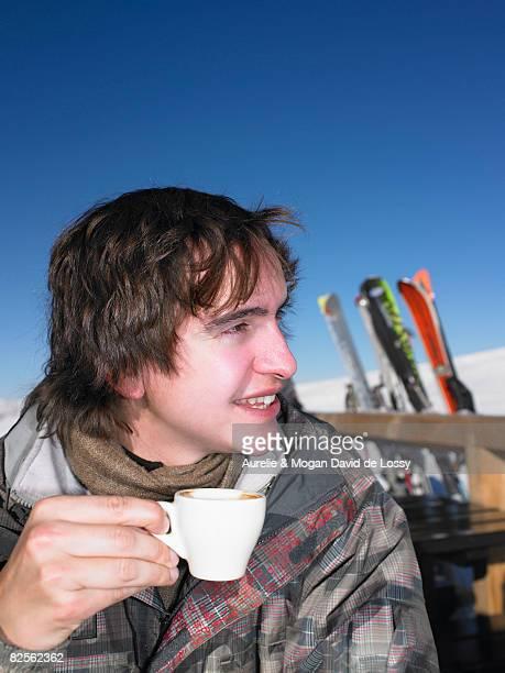 Man drinking hot drink at ski resort