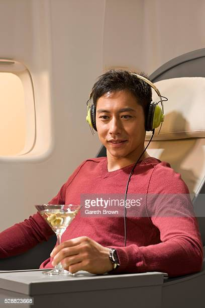 Man drinking martini and listening to music on airplane