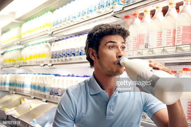 Man drinking milk in front of fridge in a supermarket