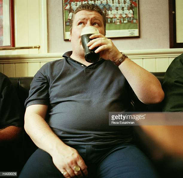 man drinking pint in pub, close-up - pancia gonfia foto e immagini stock