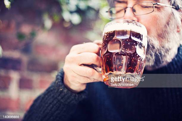 Man drinking pint of beer.