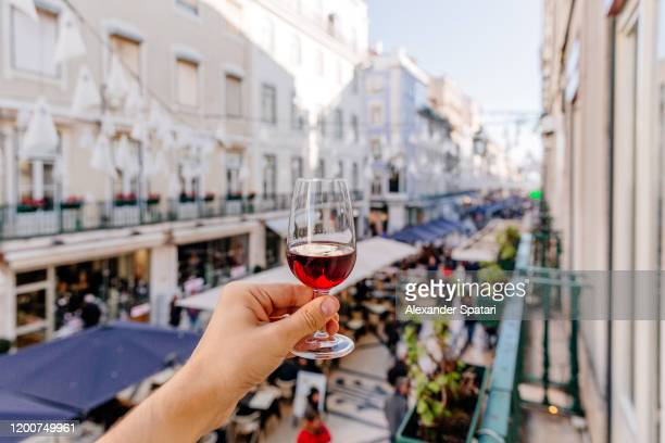 man drinking port wine on a street in lisbon, personal perspective view, lisbon, portugal - portugal stock pictures, royalty-free photos & images