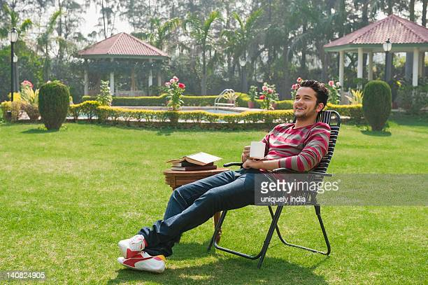 Man drinking tea and day dreaming in a garden