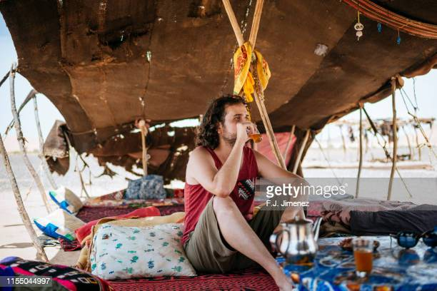 man drinking tea in berber tent in merzouga, morocco - nomadic people stock pictures, royalty-free photos & images