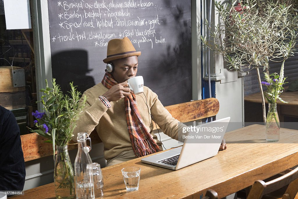 Man drinking tea while at laptop in urban cafe. : Stock Photo