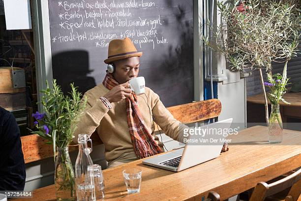 Man drinking tea while at laptop in urban cafe.