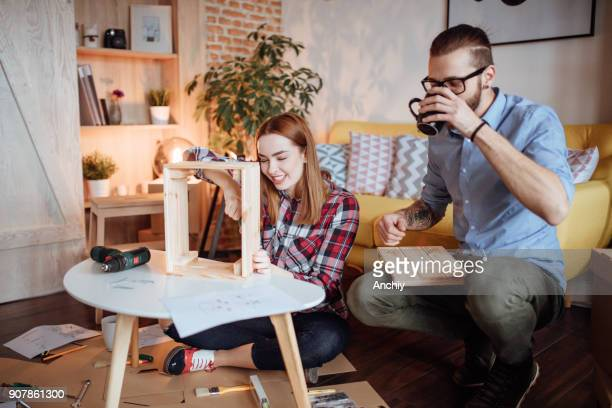 Man drinking tea while his wife assembling crate