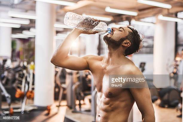 Hombre agua potable después de hacer ejercicio en el gimnasio.