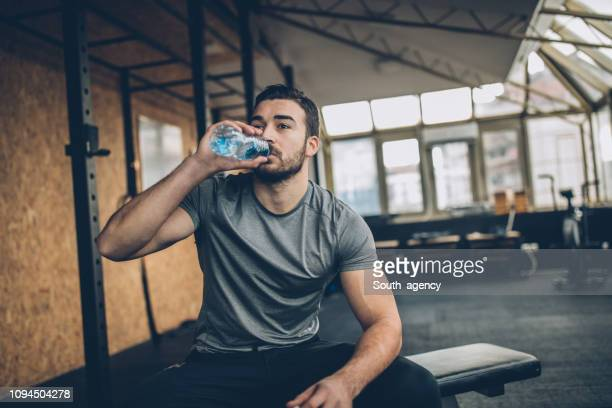 man drinking water after training in gym - drink water stock pictures, royalty-free photos & images