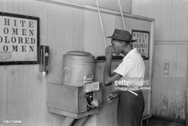 "Man Drinking Water at ""Colored"" Water Cooler in Bus Terminal, Oklahoma City, Oklahoma, USA, Russell Lee, Farm Security Administration, July 1939."