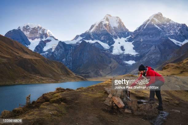 man drinking water from faucet at huayhuash campsite, queropalca, huanuco, peru, huanuco region - paisajes de peru fotografías e imágenes de stock
