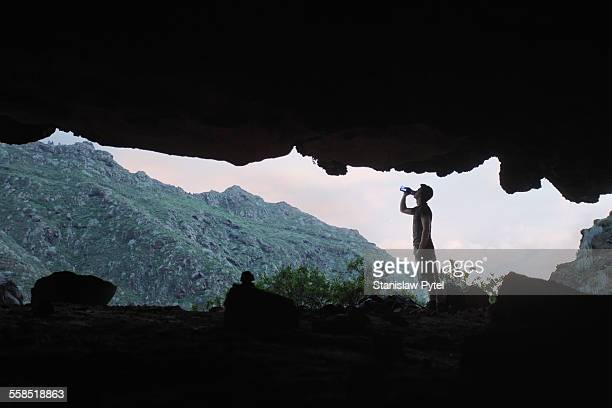 Man drinking water in mountains, view from cave