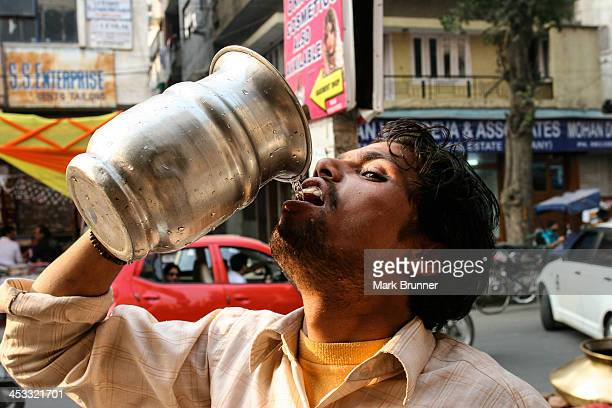 Man drinking water on a hot day from a silver colored metal jug.