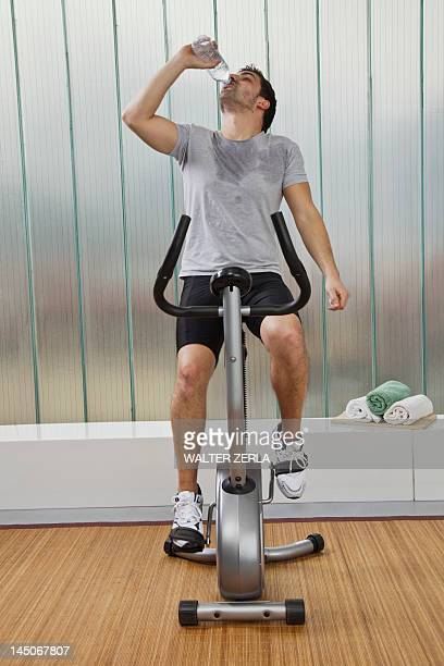 man drinking water on exercise machine - peloton stock pictures, royalty-free photos & images