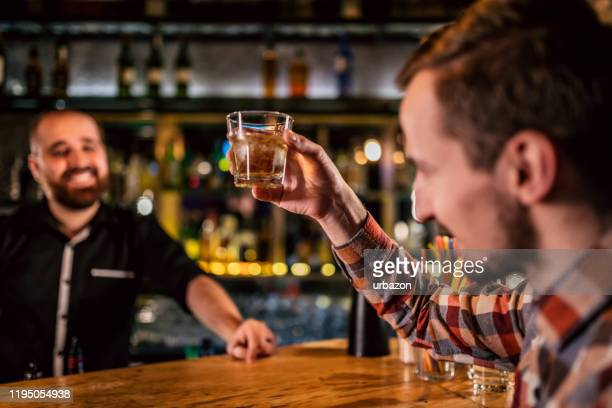 man drinking whiskey in bar - scotch whiskey stock pictures, royalty-free photos & images