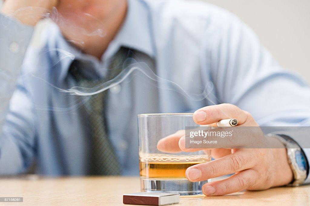 Man drinking whisky and smoking : Stock Photo