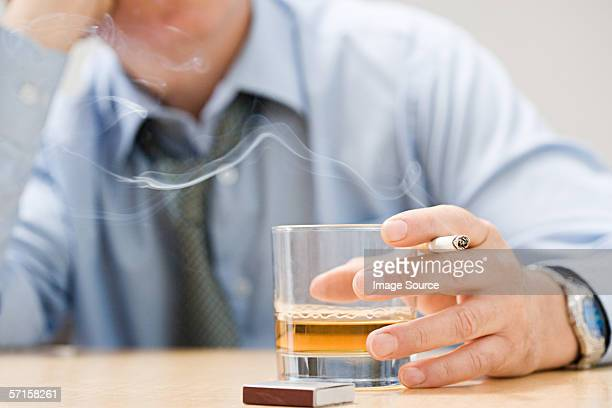 man drinking whisky and smoking - verslaving stockfoto's en -beelden