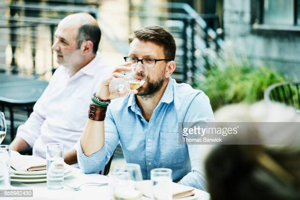 Man drinking wine while sharing dinner with friends on restaurant patio