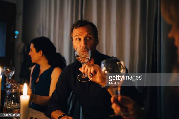man drinking wine while sitting with female friends at dinner party - woman sitting on man's lap stock pictures, royalty-free photos & images