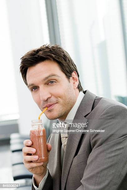 man drinking with straw from a bottle - mid volwassen mannen stockfoto's en -beelden