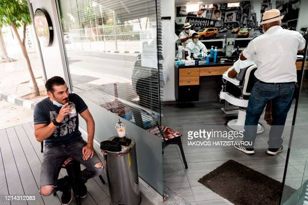 A man drinks a chilled coffee drink outside a hairdresser's salon in the Cypriot capital Nicosia on May 21 on the first day of educational facilities...