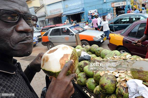 A man drinks a coconut water by the roadeside on the eve of presidential elections in Accra on December 6 2008 Thousands of Ghanaians held colourful...