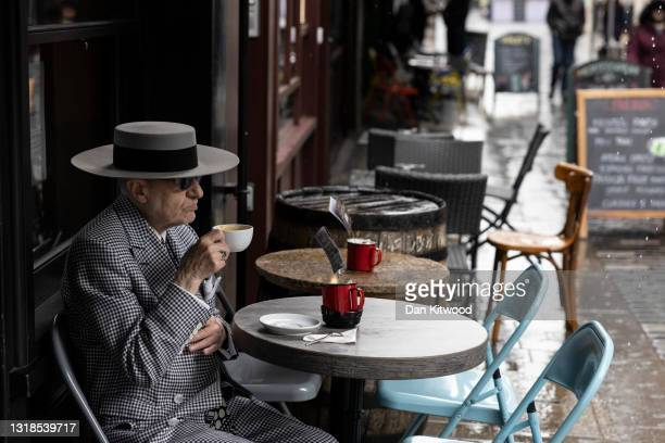 Man drinks a coffee at a cafe in Soho on May 17, 2021 in London, United Kingdom. From today, covid restrictions on indoor activities and household...